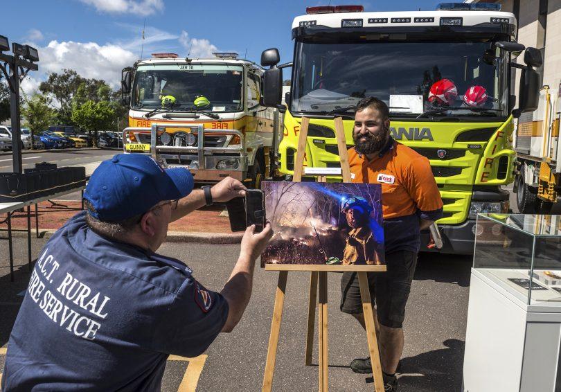 Volunteer firefighter posing with artwork in front of firetruck.