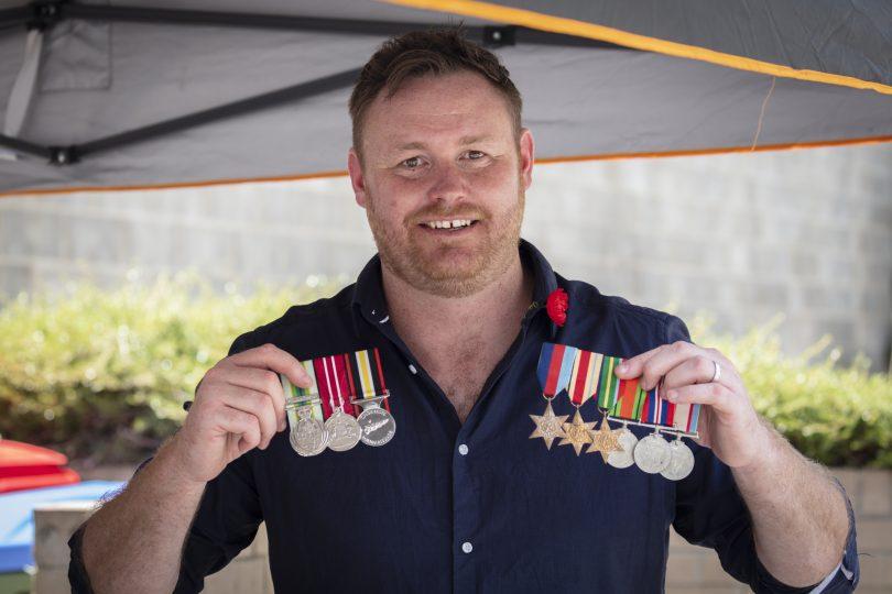 Kris Milne holding Australian Defence Force service medals.