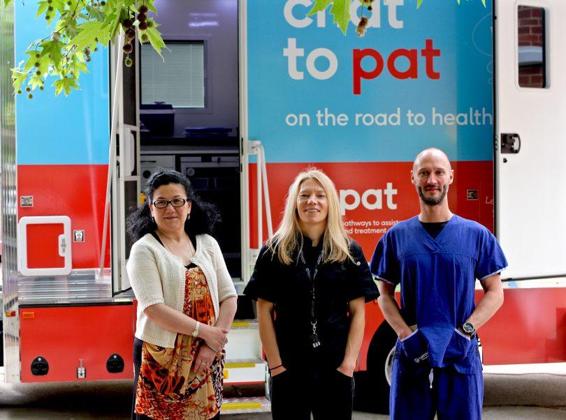 Nurgul Sawut, Ali Loom and Dr Ben Harkness standing in front of PAT van.