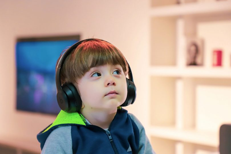 Child with headphones listening to music.