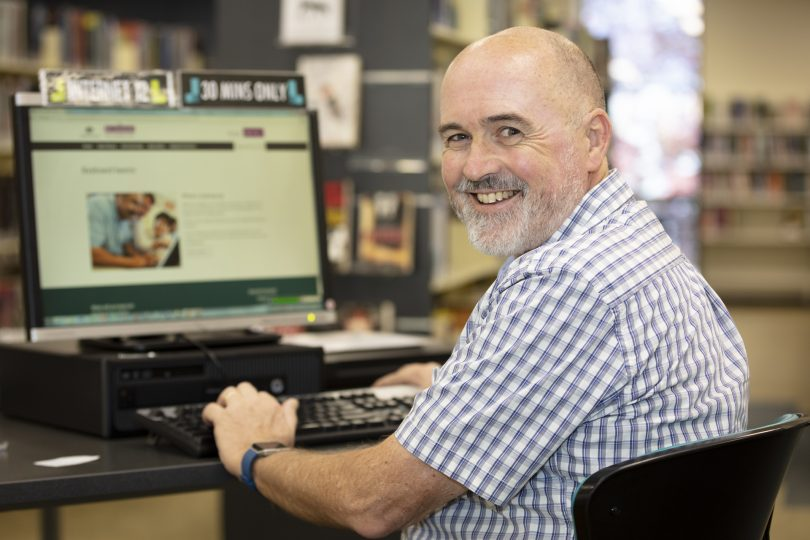Woden Community Service digital literacy mentor John Dyer sitting at computer.
