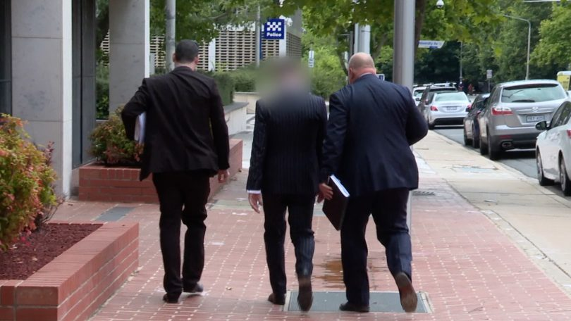 Criminal investigators from ACT Policing with one of the men arrested over alleged organised crime.