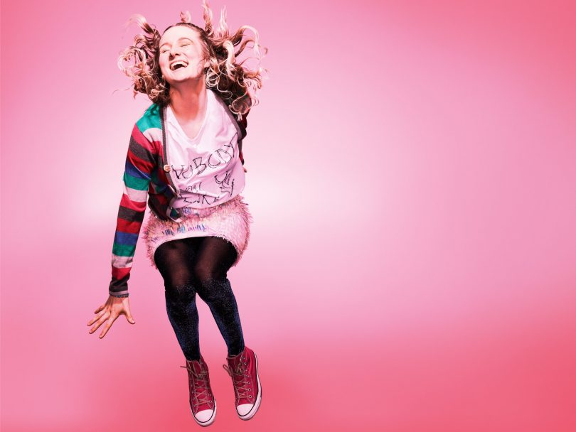 The main character Edna, a teenage girl, jumps joyously in the air in front of a pink backdrop