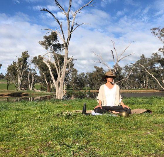 Danette Watson meditating in bush.