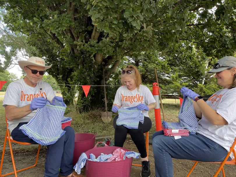 Orange Sky volunteers folding clothes.
