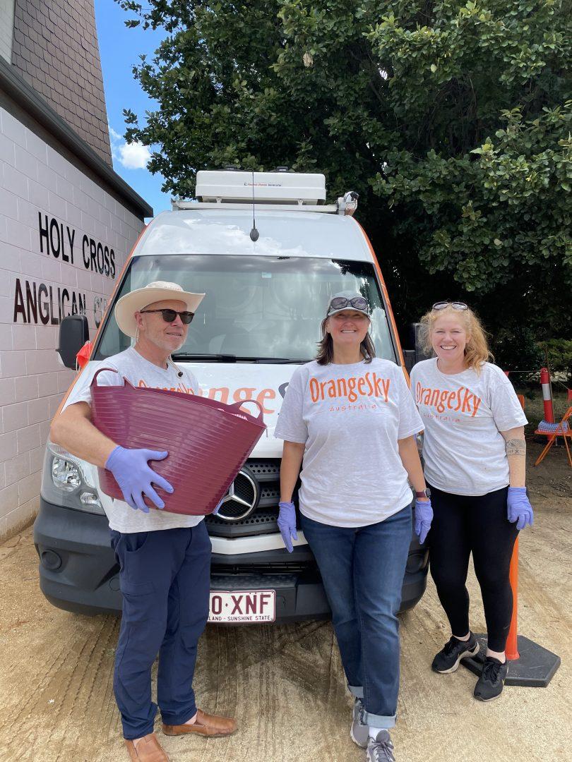 Kevin Jones, Emily Foster and Nicole Vonarx in front of Orange Sky van.