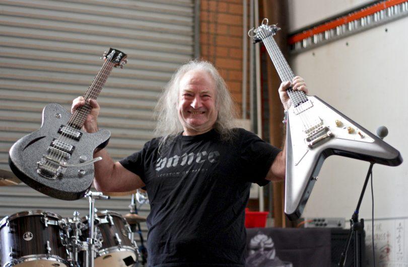 Rusty Vance holding two custom guitars in his Fyshwick workshop.