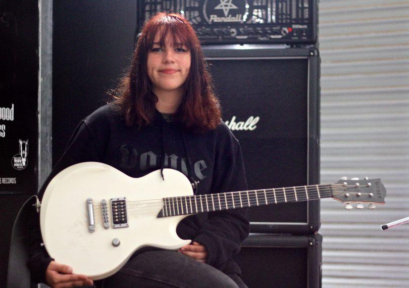 Liv McMahon holding guitar.