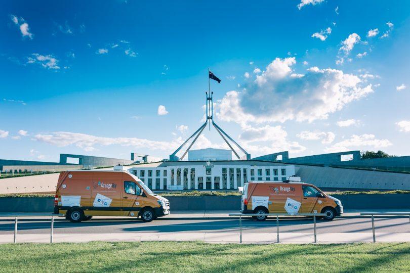 Orange Sky vans in front of Parliament House.