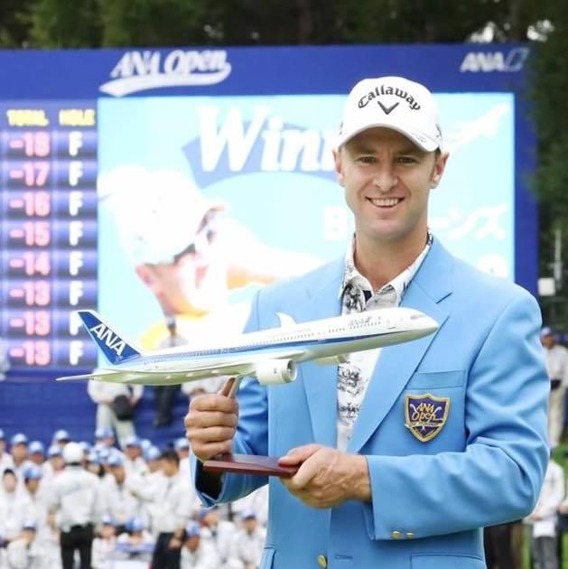 Brendan Jones holding aeroplane trophy at ANA Open in Japan.