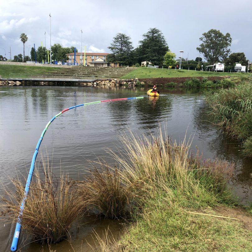 Queanbeyan SES volunteer in boat installing pool noodles across Queanbeyan River.