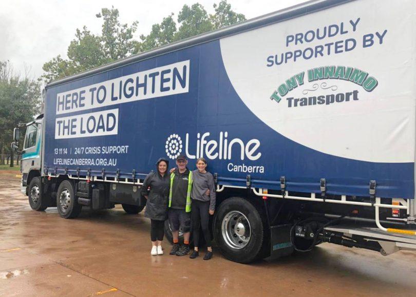 Jenine Woodman, Winnie Dennis and truck driver Jamie standing next to truck.
