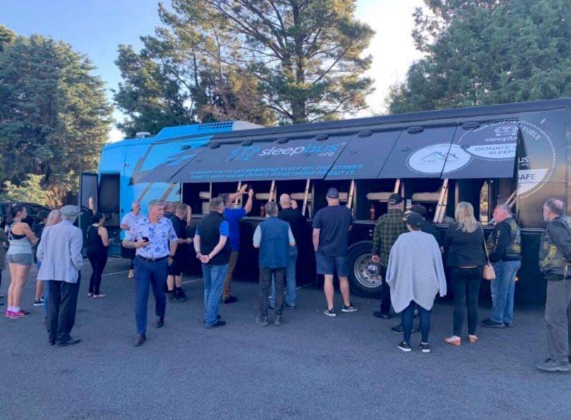 People standing in front of the sleepbus