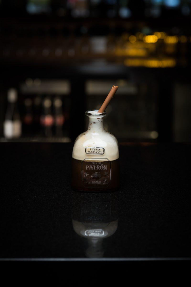Tequila bottle on a dark bar.
