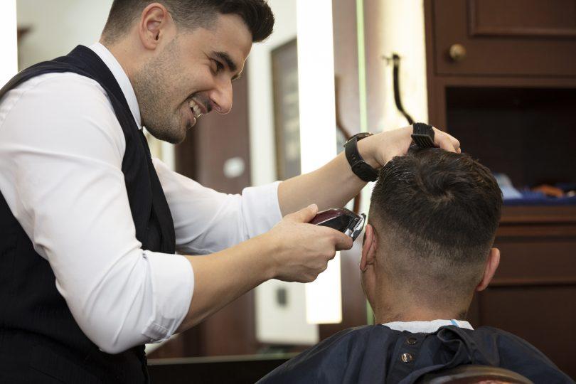 Barber cutting man's hair at Truefitt & Hill