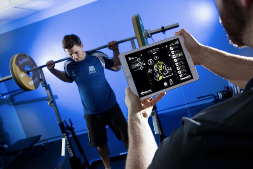 Man lifting weights while computer measures his output