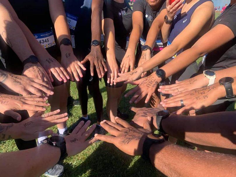 Indigenous Marathon Foundation members placing hands in circle