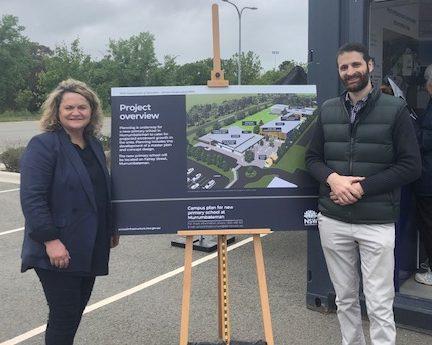 Wendy Tuckerman standing next to project-overview sign for Murrumbateman primary school