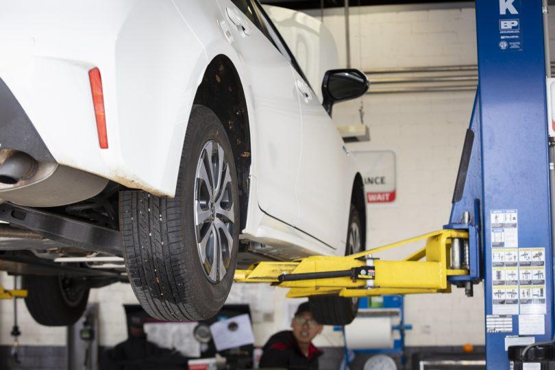 Car on hoist being serviced at workshop