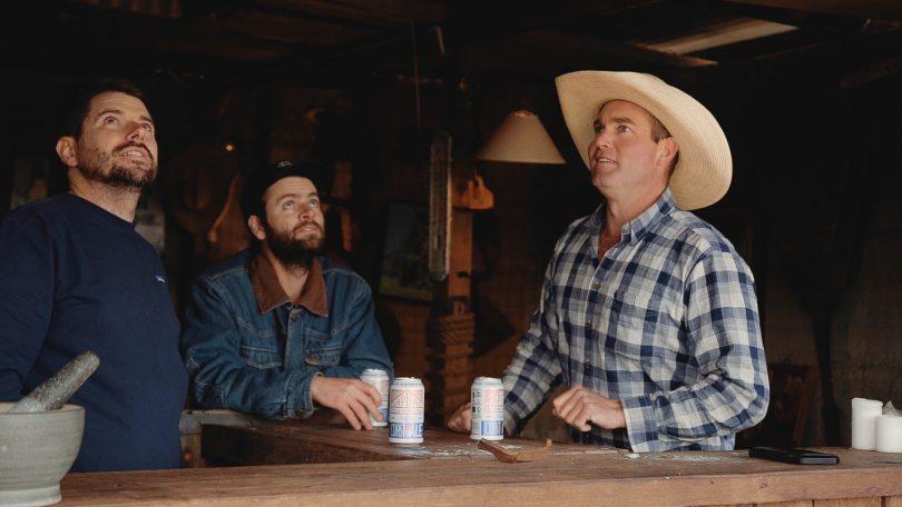 Three men drinking beer and looking upwards