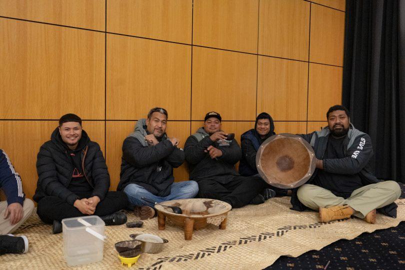 Pacific Islander men sitting on floor drinking kava