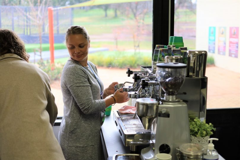 Woman using coffee machine at The Nest cafe at Evatt Primary School