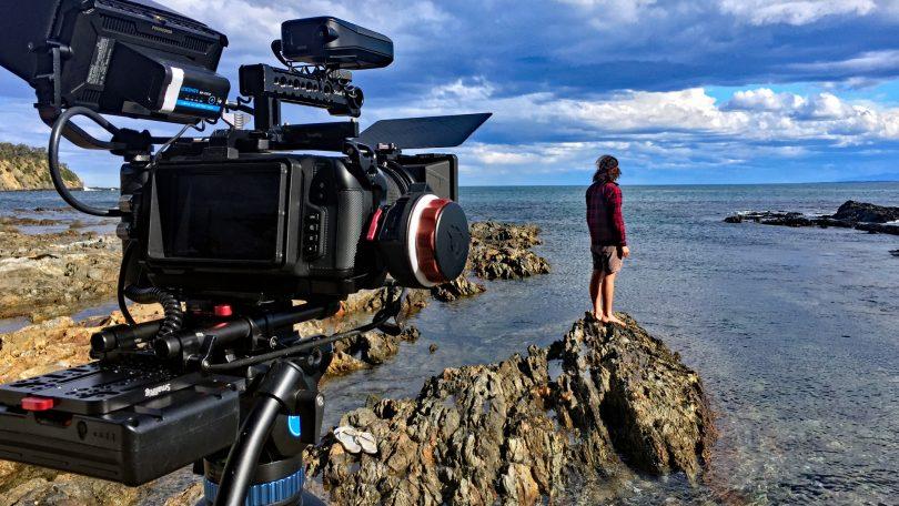 Camera filming man standing on coastal rocks