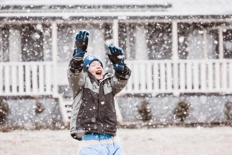 A boy smiles as he plays in falling snow