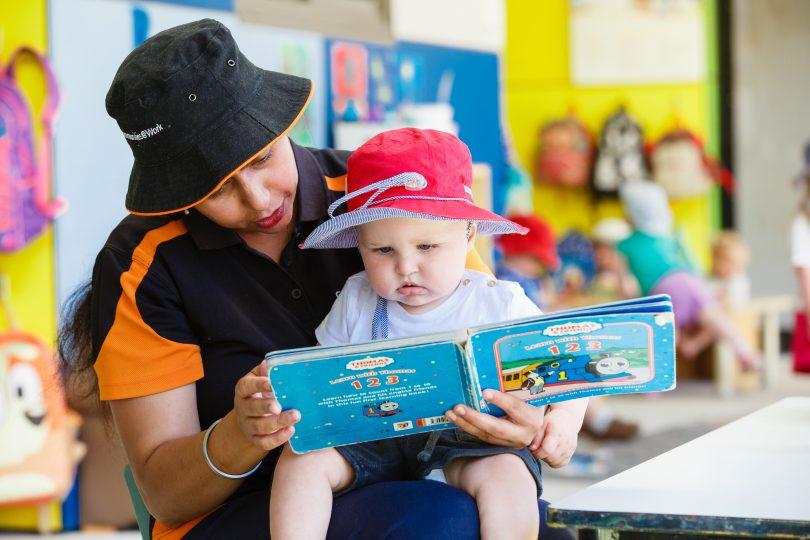 Communities@Work educator reading book to child