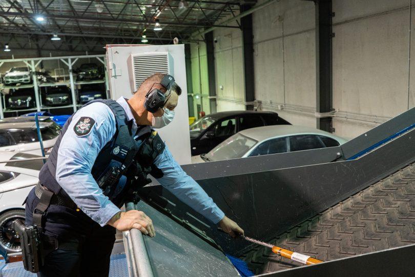 Police officer shredding a seized firearm