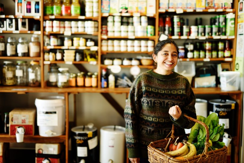 Woman in The Food Co-op holding basket of food