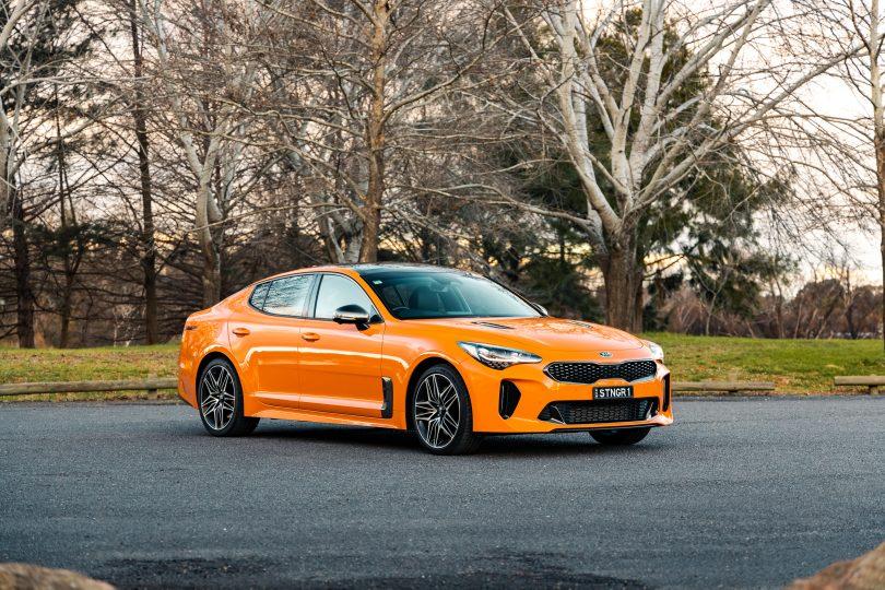 Orange Kia Stinger GT car parked in front of trees