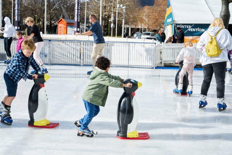 boy pushing penguin on ice