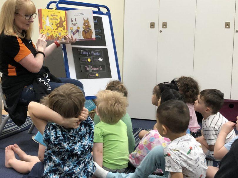 Communities@Work educator reading book to children