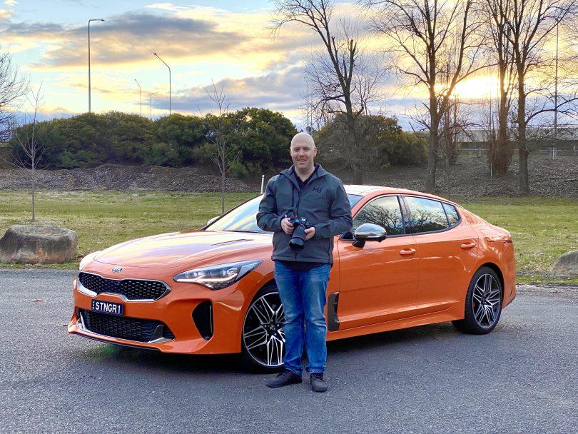 Michael Briguglio standing in front of orange 2021 Kia Stinger GT car