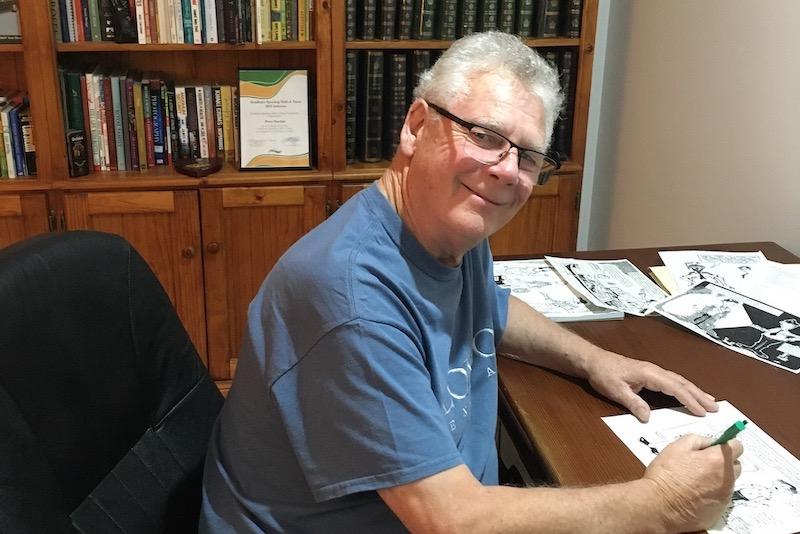 Peter Sinclair drawing cartoon at desk