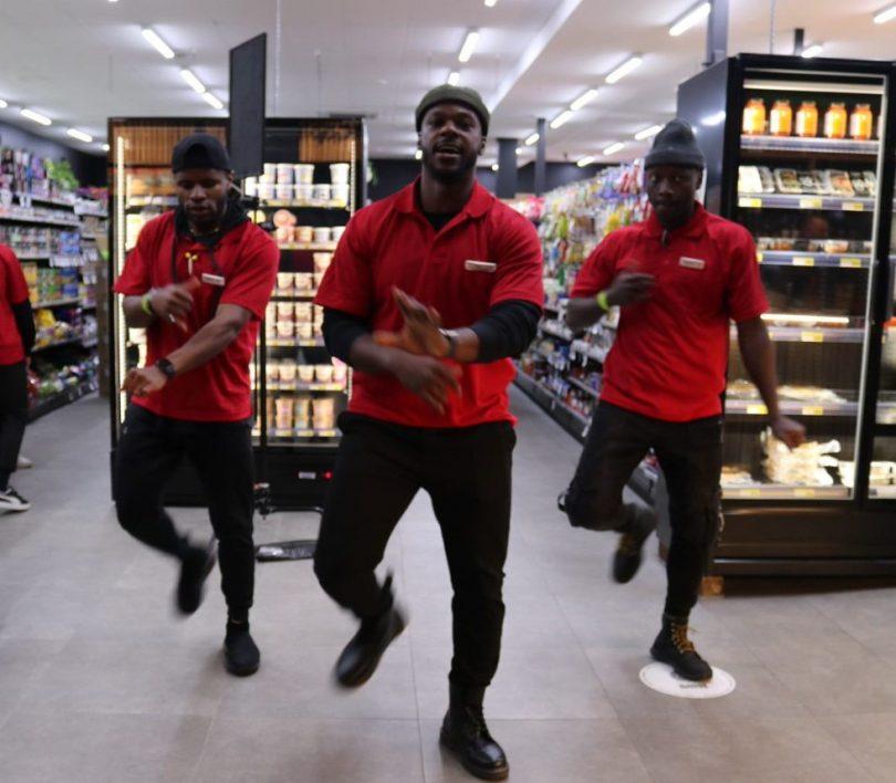 three men dance in store