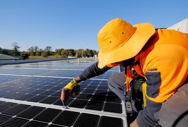 Man installing solar system on rooftop