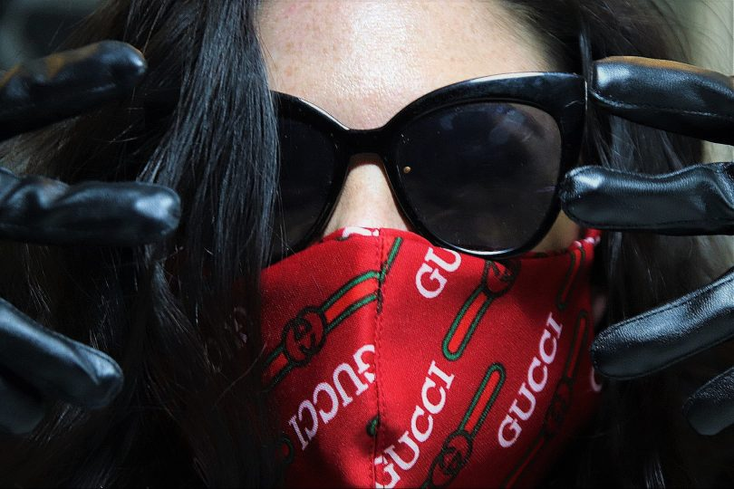 A woman in sunglasses wears a red Gucci face mask