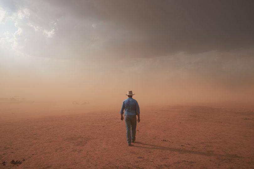 Farmer walking through dust storm