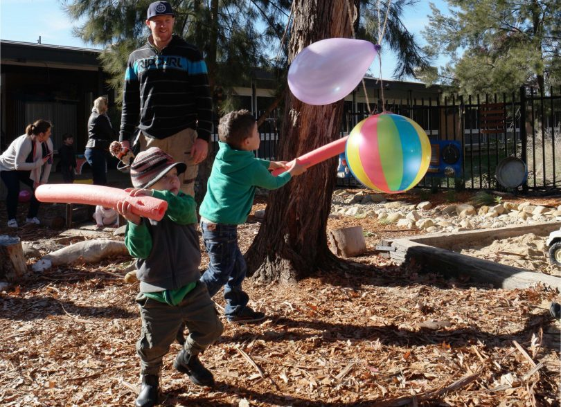 Child hits balloon with noodle