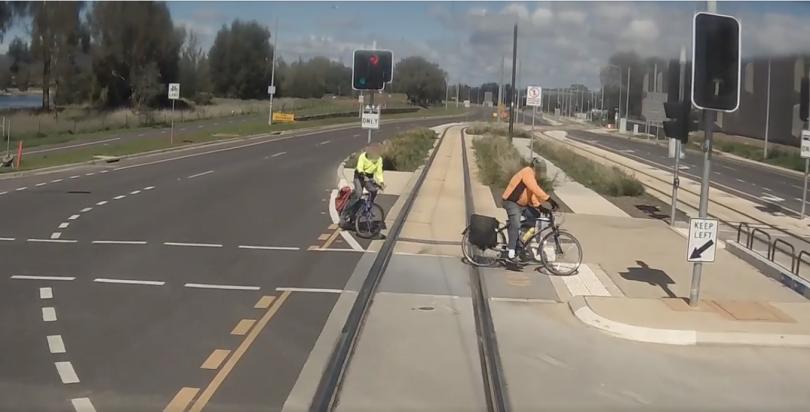 Bikes in front of tram on light rail tracks
