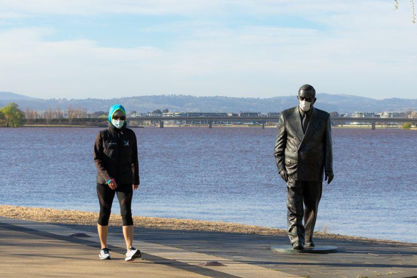 Woman walking along Lake near Sir Robert Menzies statue.