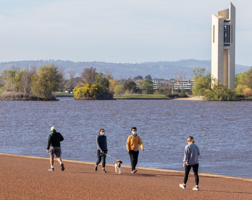 People walking by lake.