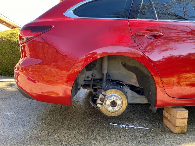 Car hoisted on bricks with wheel missing