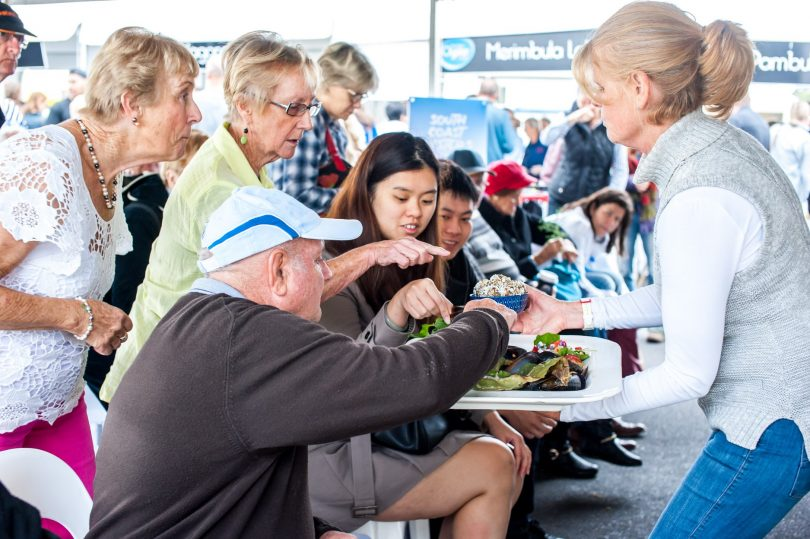 Samples are handed to the crowd during a cooking demonstration at 2018's Narooma Oyster festival. Picture: provided.