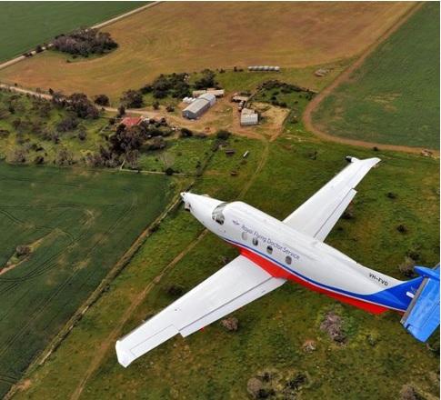 Aerial image of Royal Flying Doctor Service plane flying over rural land.