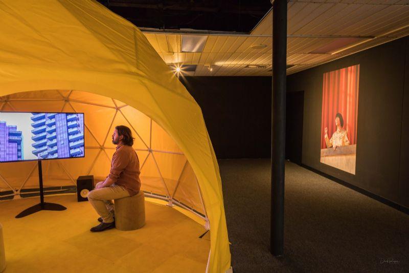 Man sitting inside The Ambassador exhibition at Bega Valley Regional Gallery.
