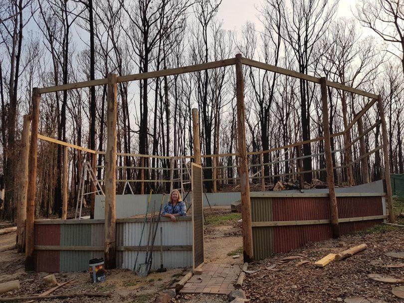 Lorita Baumann standing in the newly built raptor enclosure on her burnt property.