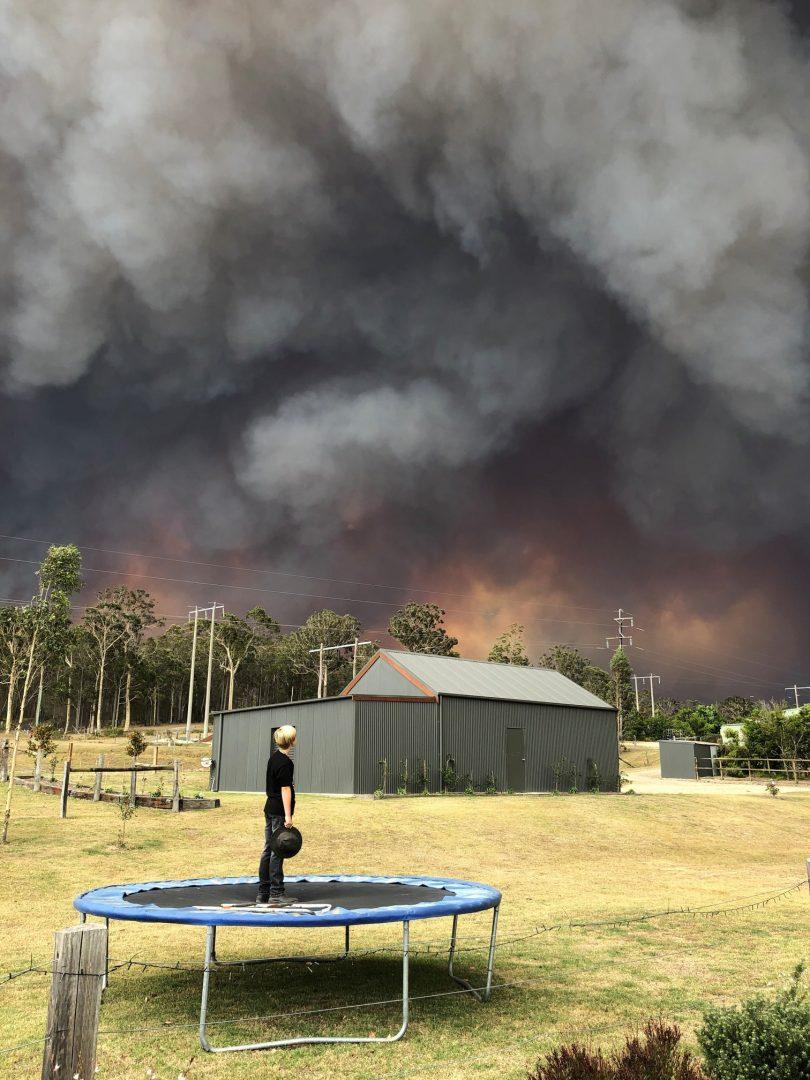 Boy on trampoline watching smoke from approaching bushfire.